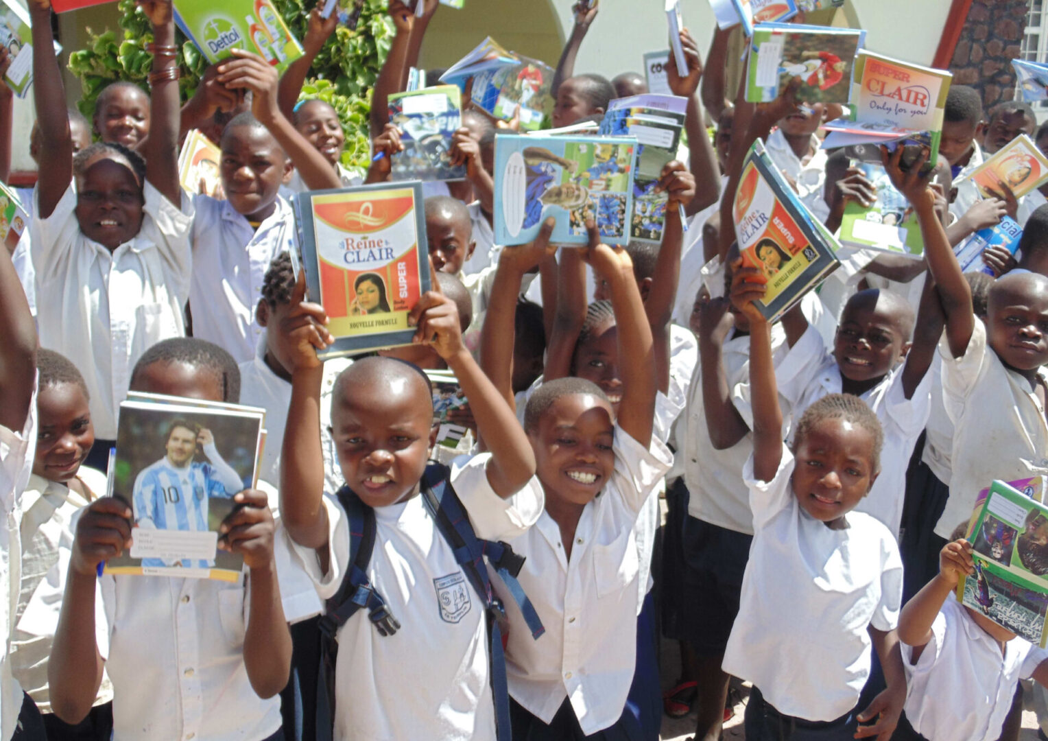 Kids smiling and raising books in the air