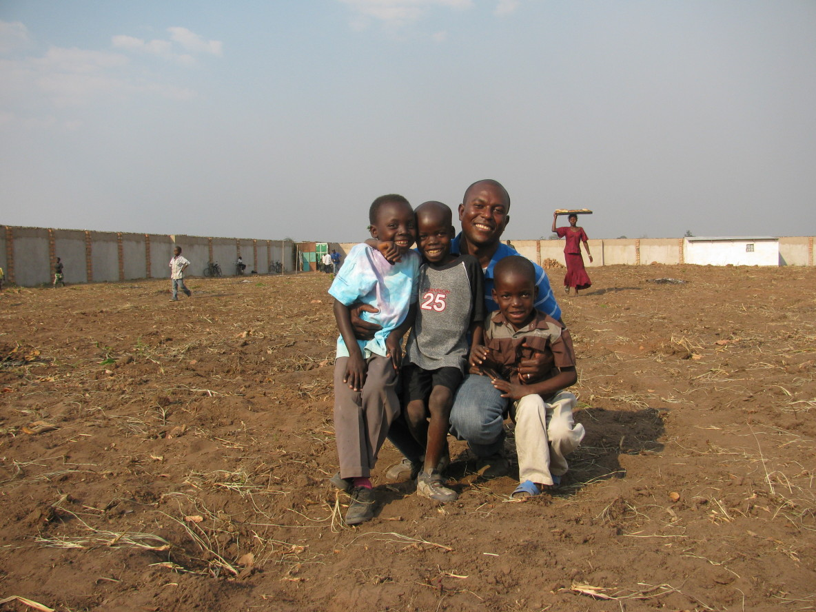 A man embracing three kids